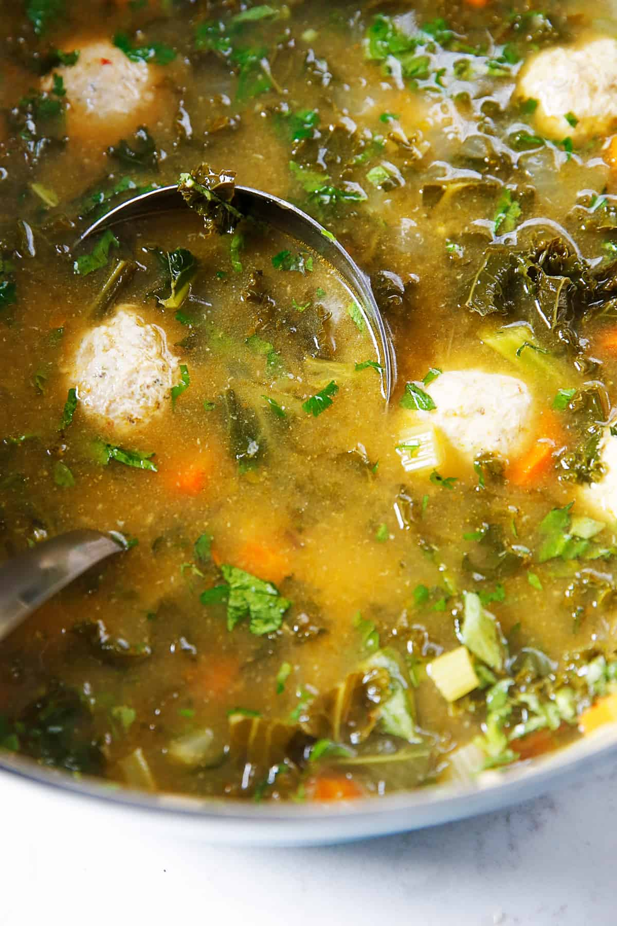 A pot of Italian wedding soup with kale.