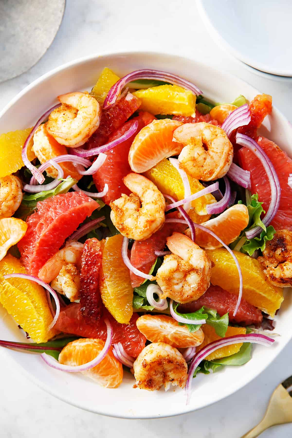 Spicy shrimp salad with citrus in a bowl.
