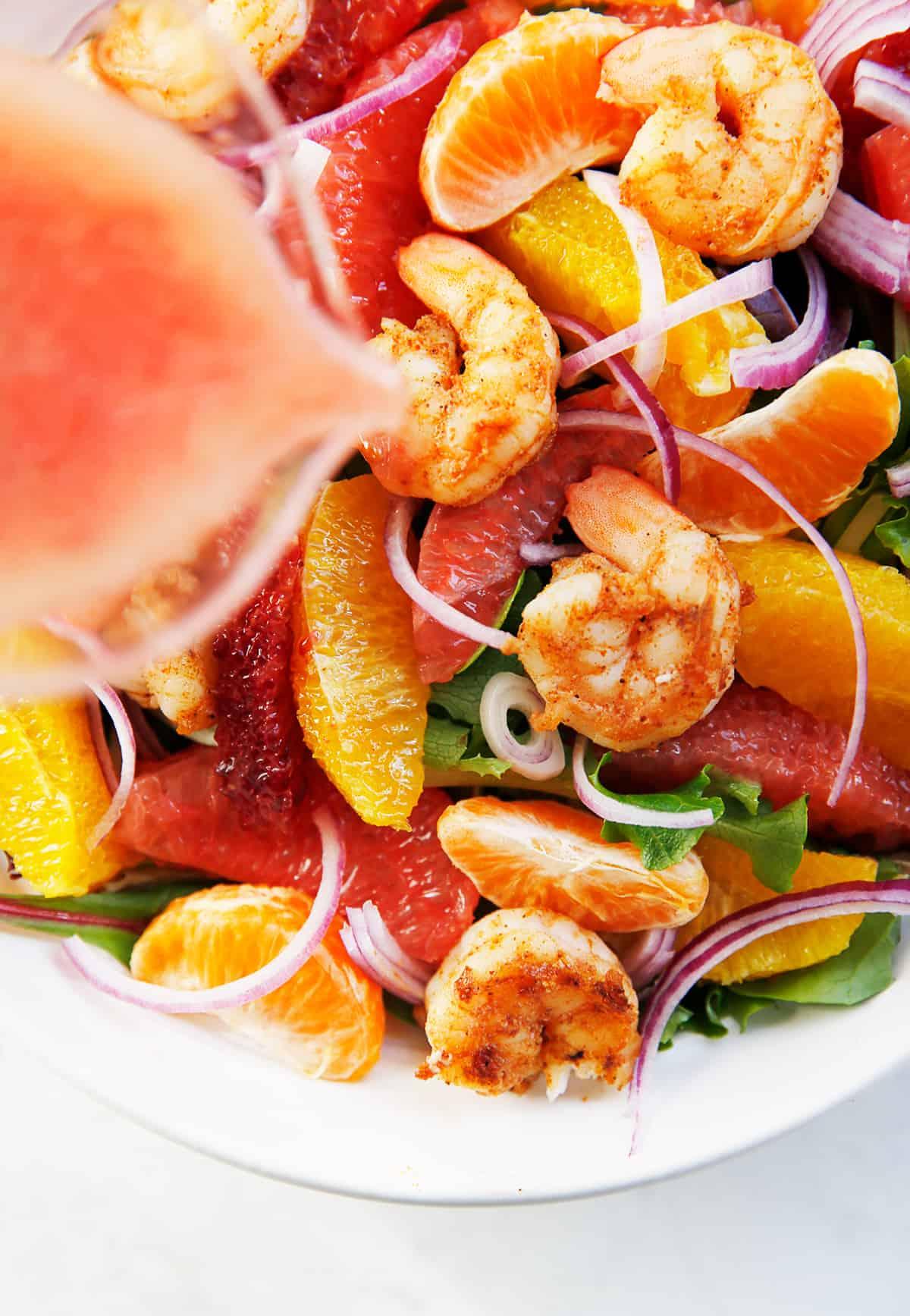 Grapefruit vinaigrette being poured over citrus shrimp salad.