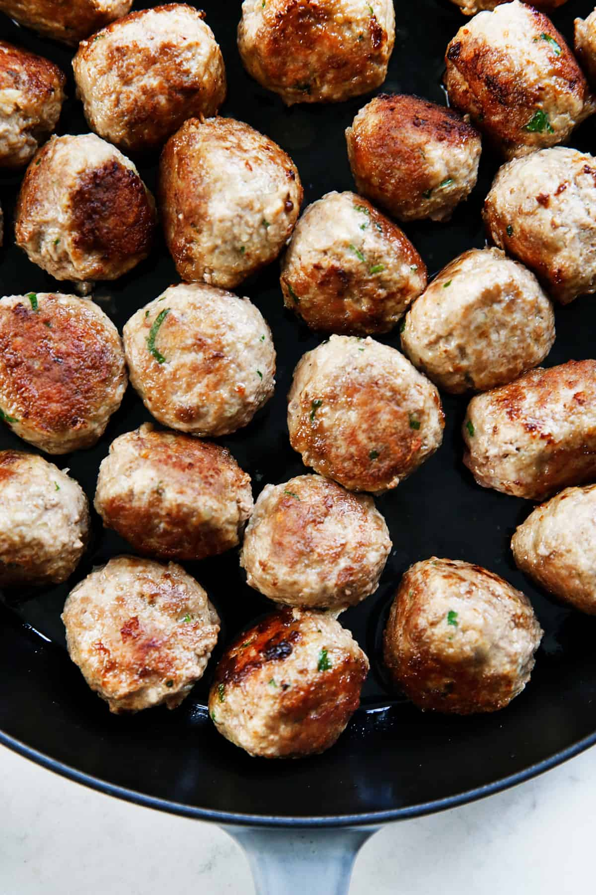 Browned meatballs in a pan.