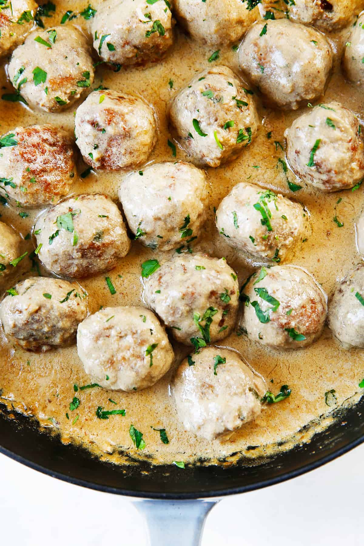 Gravy covered gluten free Swedish Meatballs in a pan.