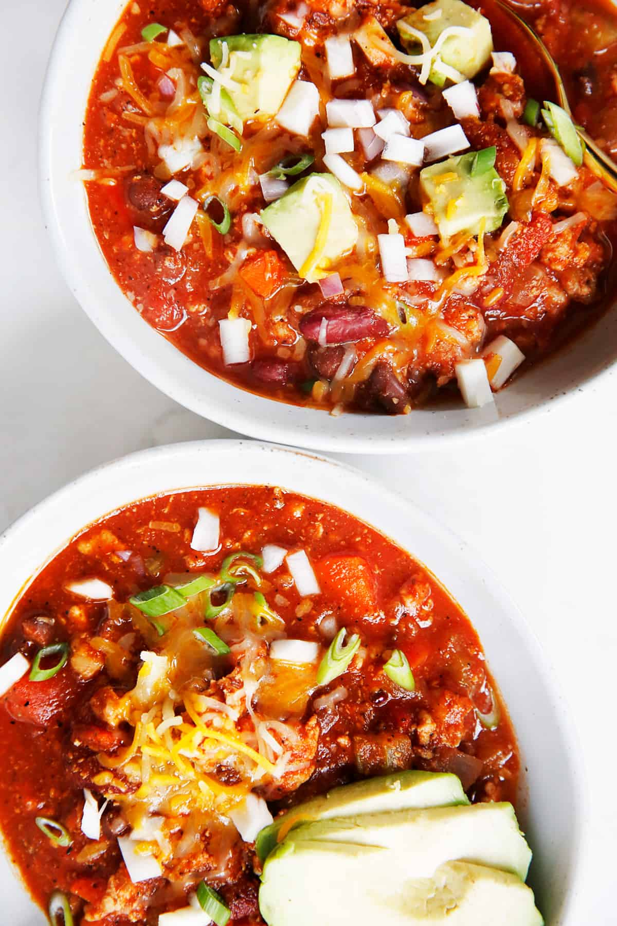 Two servings of ground turkey chili in bowls.