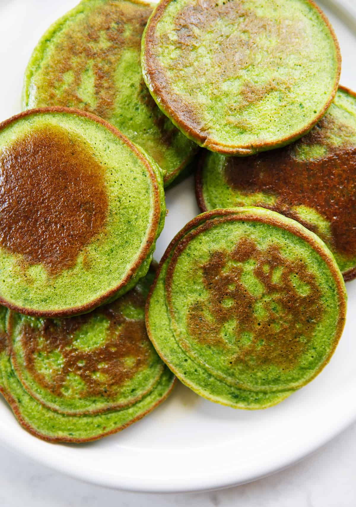 A plate full of spinach pancakes that are bright green.
