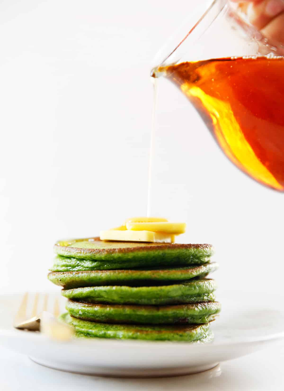 A stack of spinach pancakes with maple syrup being drizzled over the top.