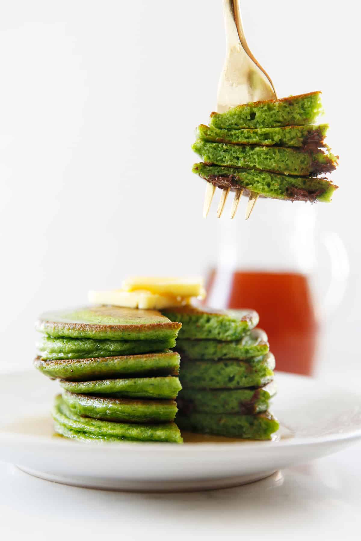 A forkful of spinach pancakes with chocolate chips.