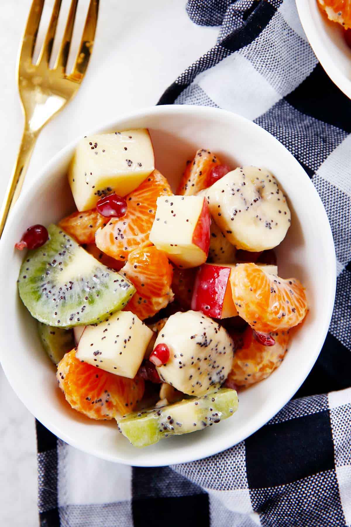 A bowl of winter fruit salad with poppy seeds and greek yogurt.