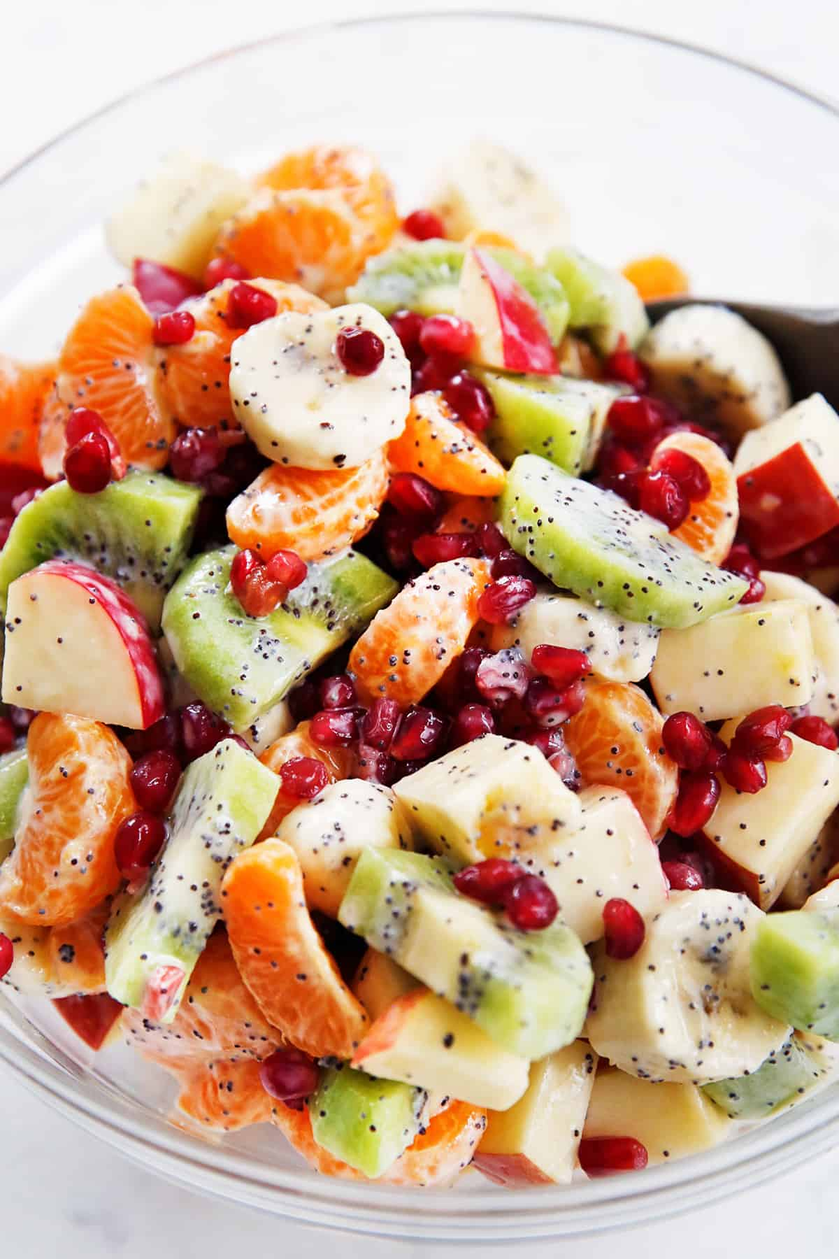 A bowl of winter fruit salad with winter fruit and greek yogurt dressing.