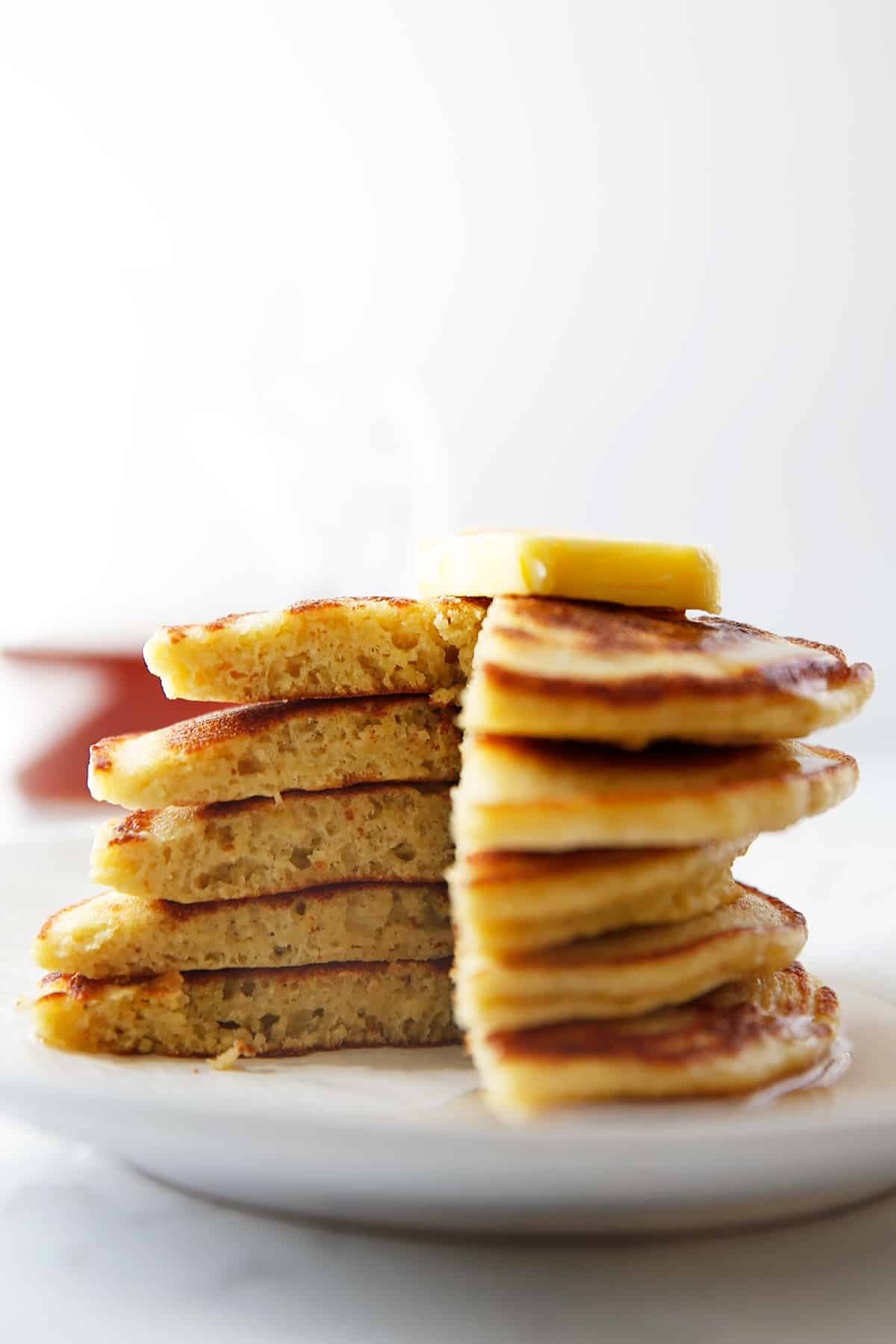 A stack of paleo pancakes with a slice taken out of them.