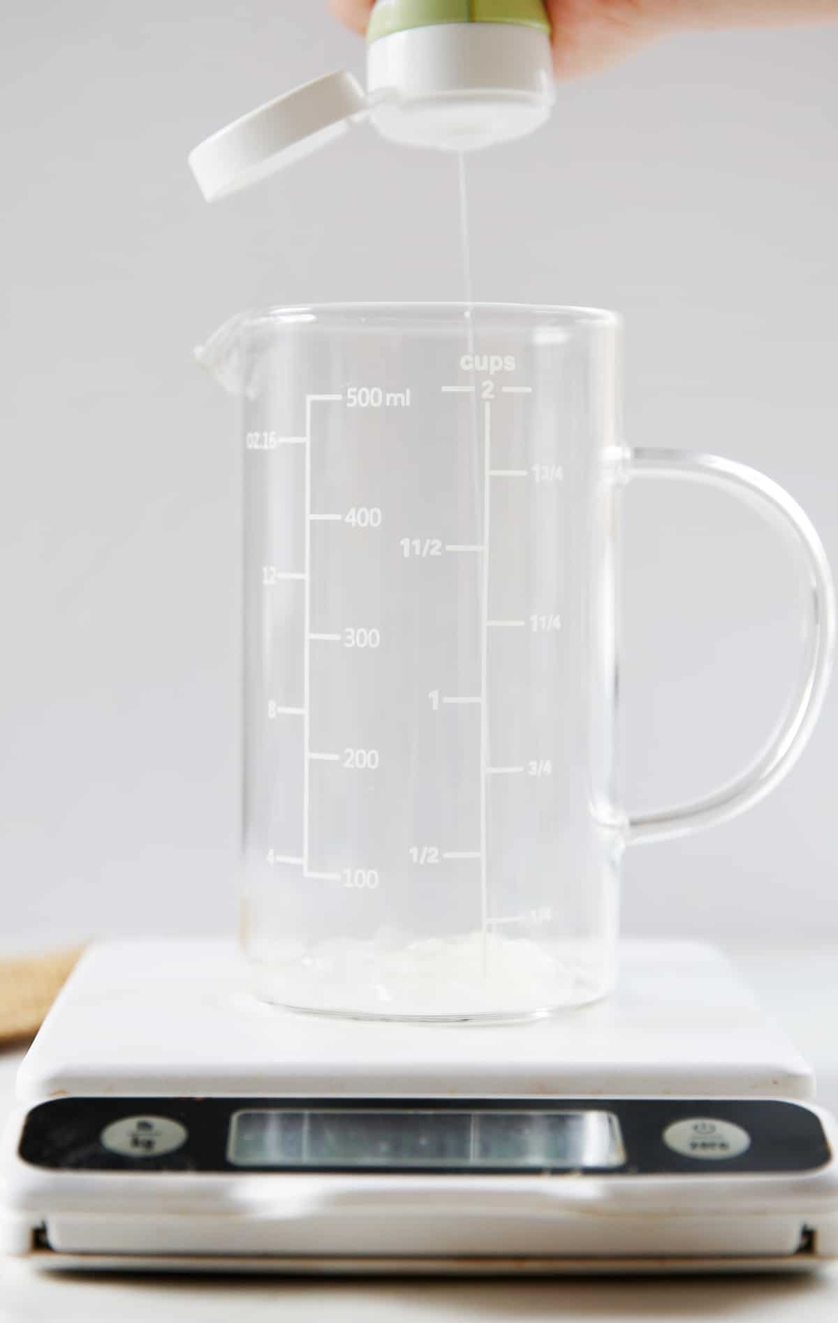 Squirting aloe vera gel into measuring cup.