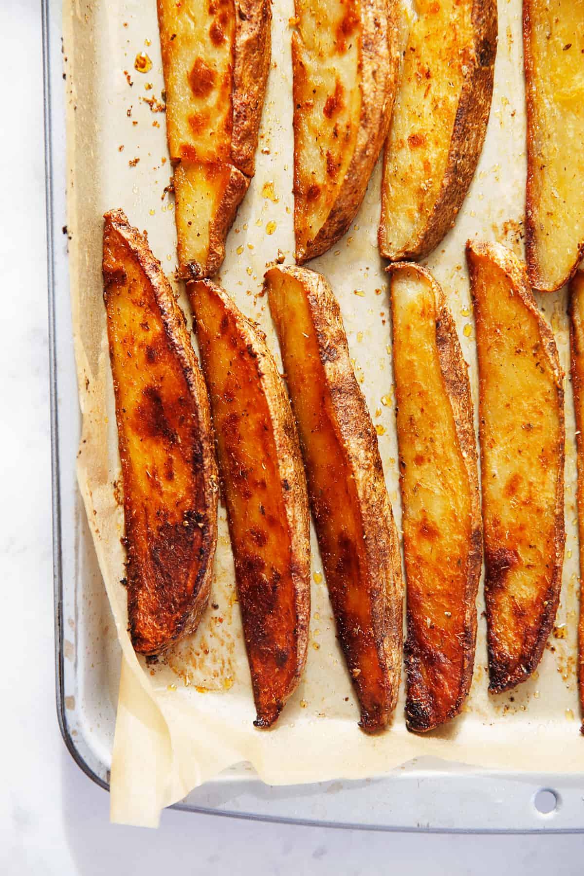 Crispy wedge potatoes on a baking sheet.