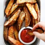 Wedge fries being dipped in ketchup.