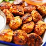 Buffalo chicken meatballs on a platter with bleu cheese.