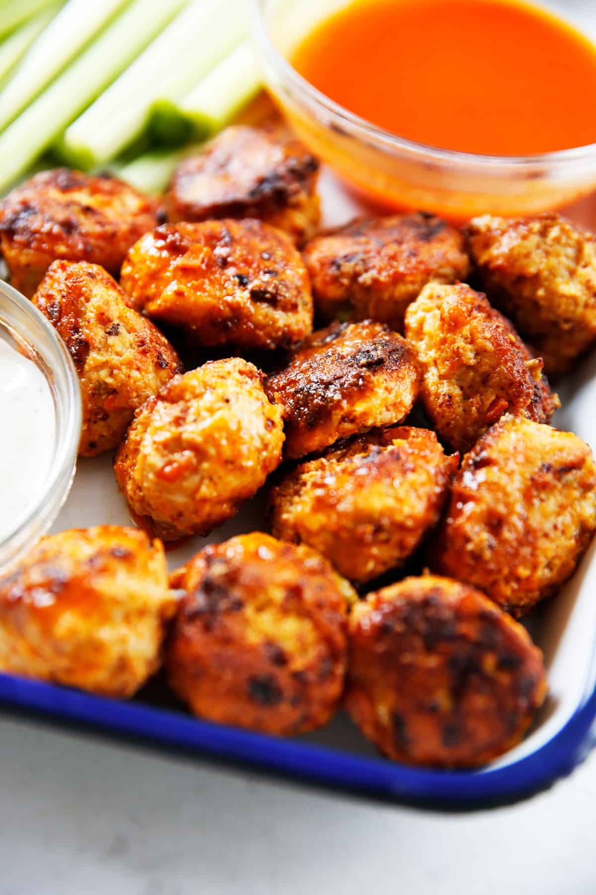 Buffalo Chicken Meatballs on a platter with extra buffalo sauce.