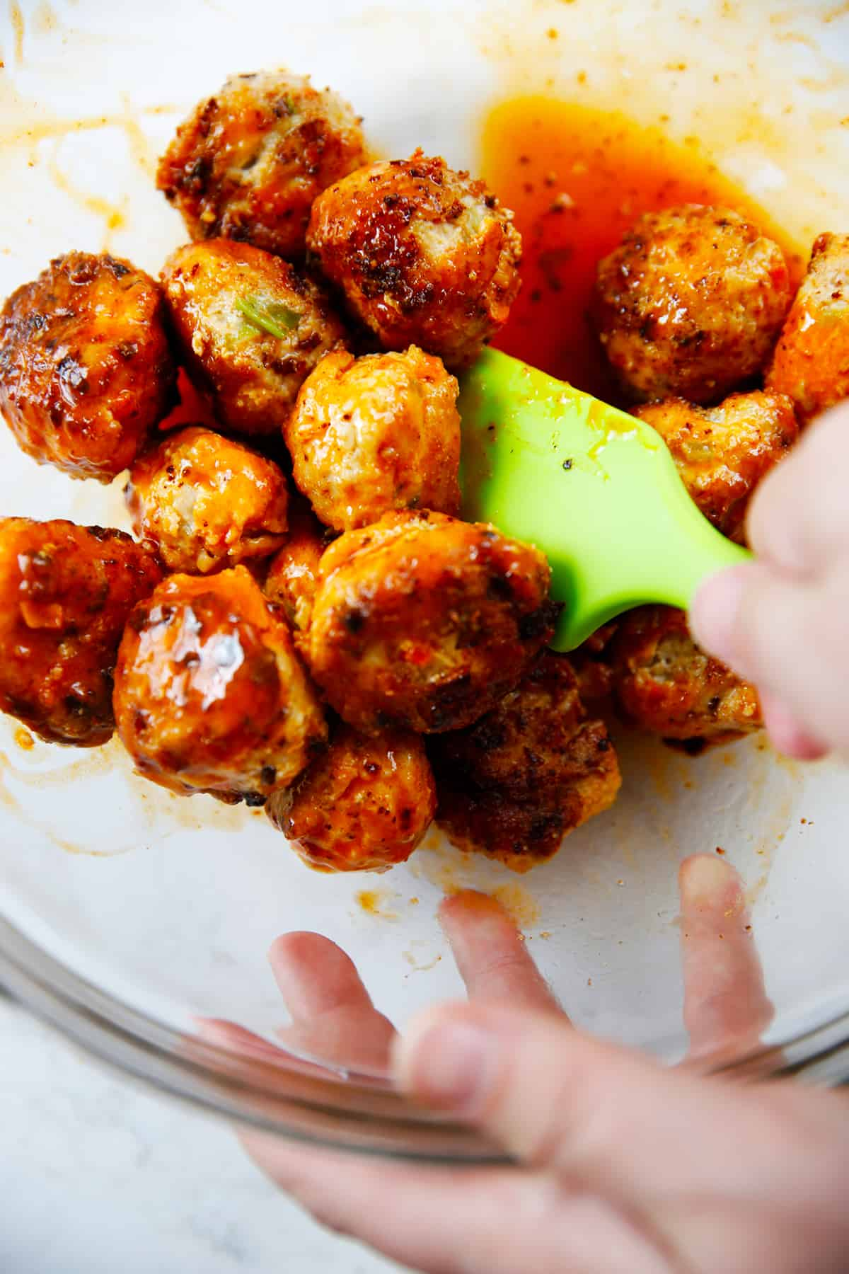 Chicken meatballs being coated in buffalo sauce in a bowl.