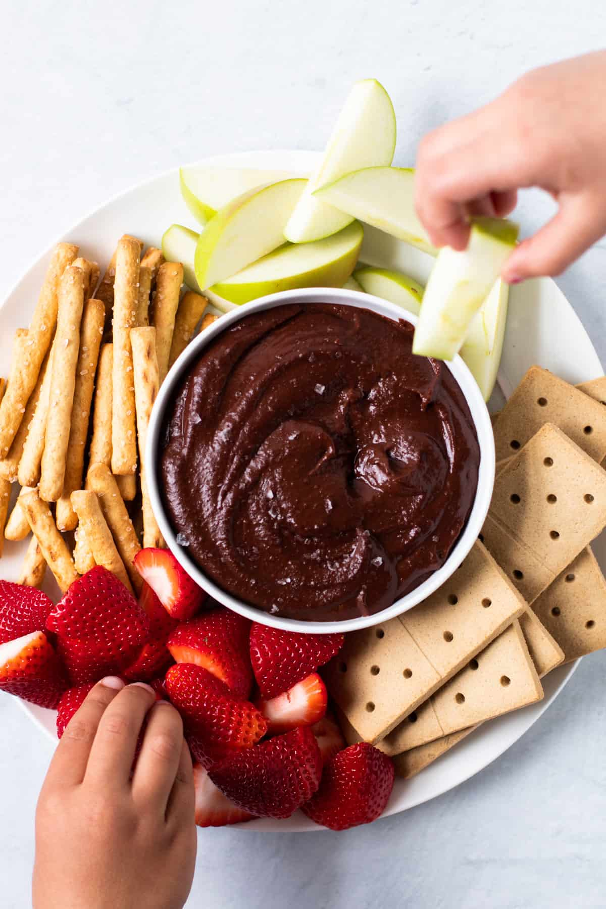 Little hands showing what to eat with chocolate hummus.