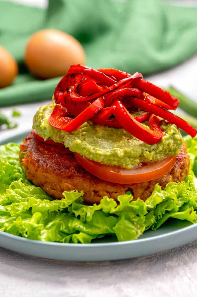 A salmon burger topped with guacamole and roasted red peppers.