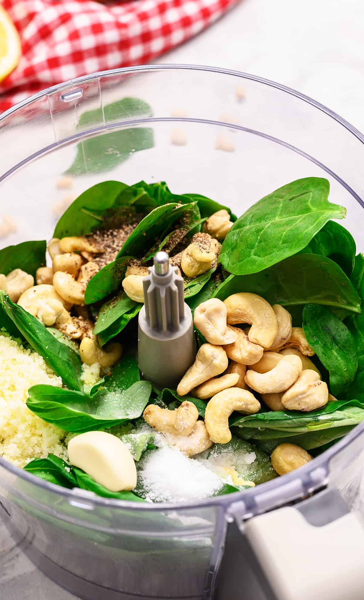 Pesto ingredients in a food processor, including nuts, garlic, spinach and basil.
