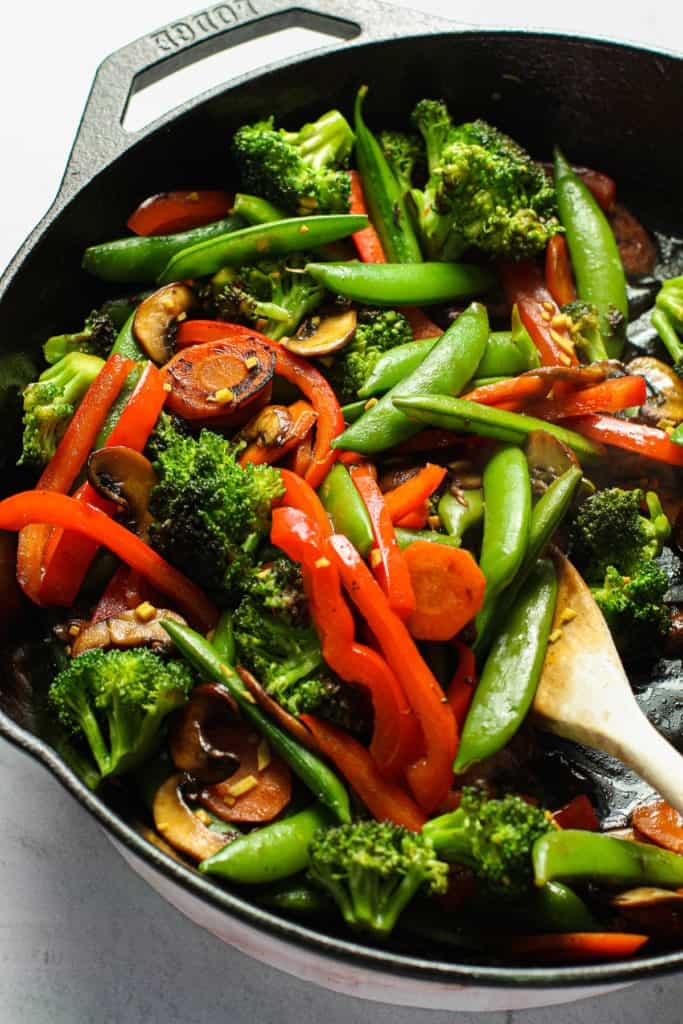 A stir fry of veggies in a cast iron skillet.