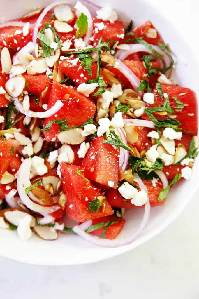 A bowl of watermelon salad with onions, herbs, cheese and nuts.