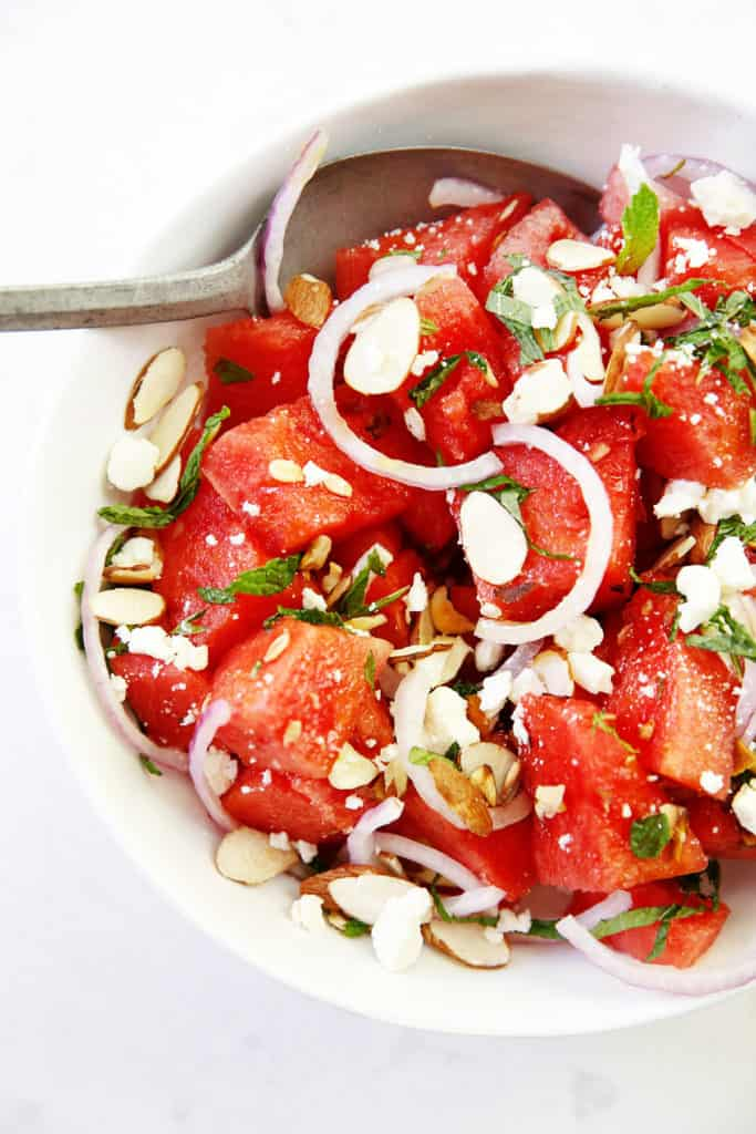 Watermelon salad with sliced onions and nuts