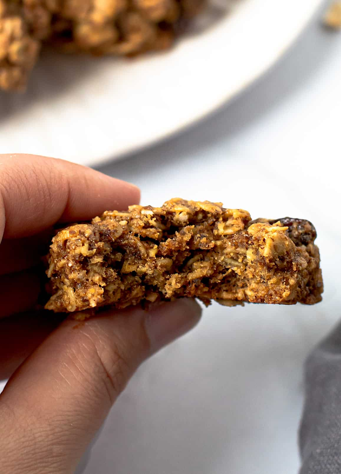 A lactation cookie with a bite taken out of it.