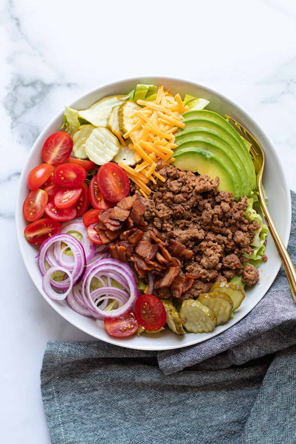 Cheeseburger salad ingredients in a bowl.