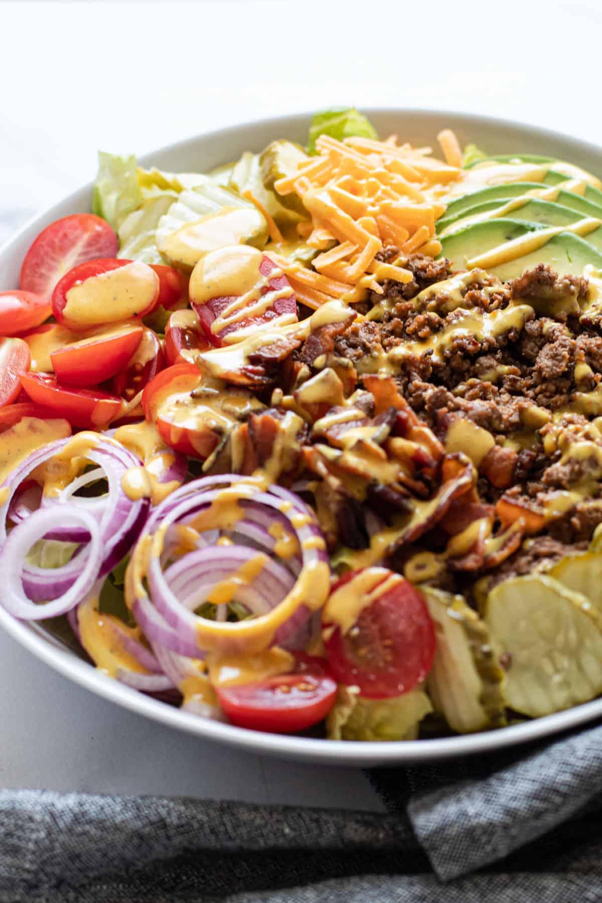 A cheeseburger salad with mustard dressing.