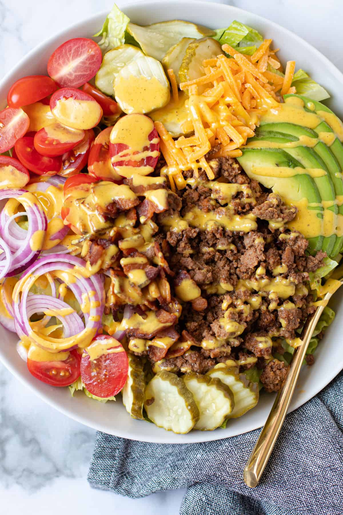 Cheeseburger salad in a bowl with mustard dressing.