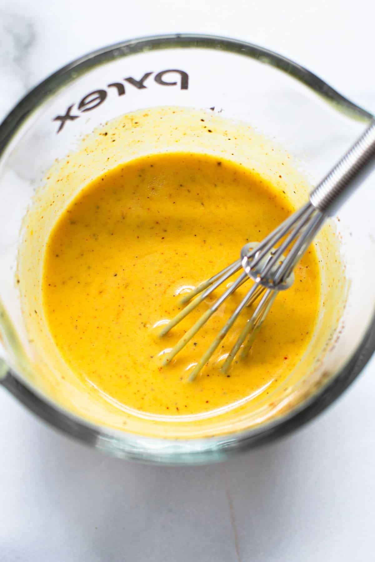 Mustard salad dressing in a glass container.