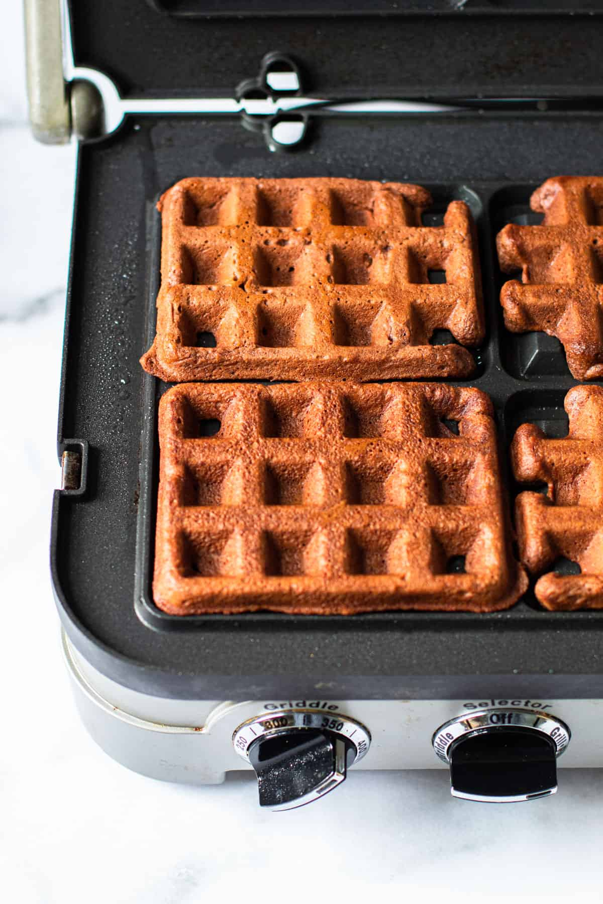 Chocolate waffles in a waffle iron.