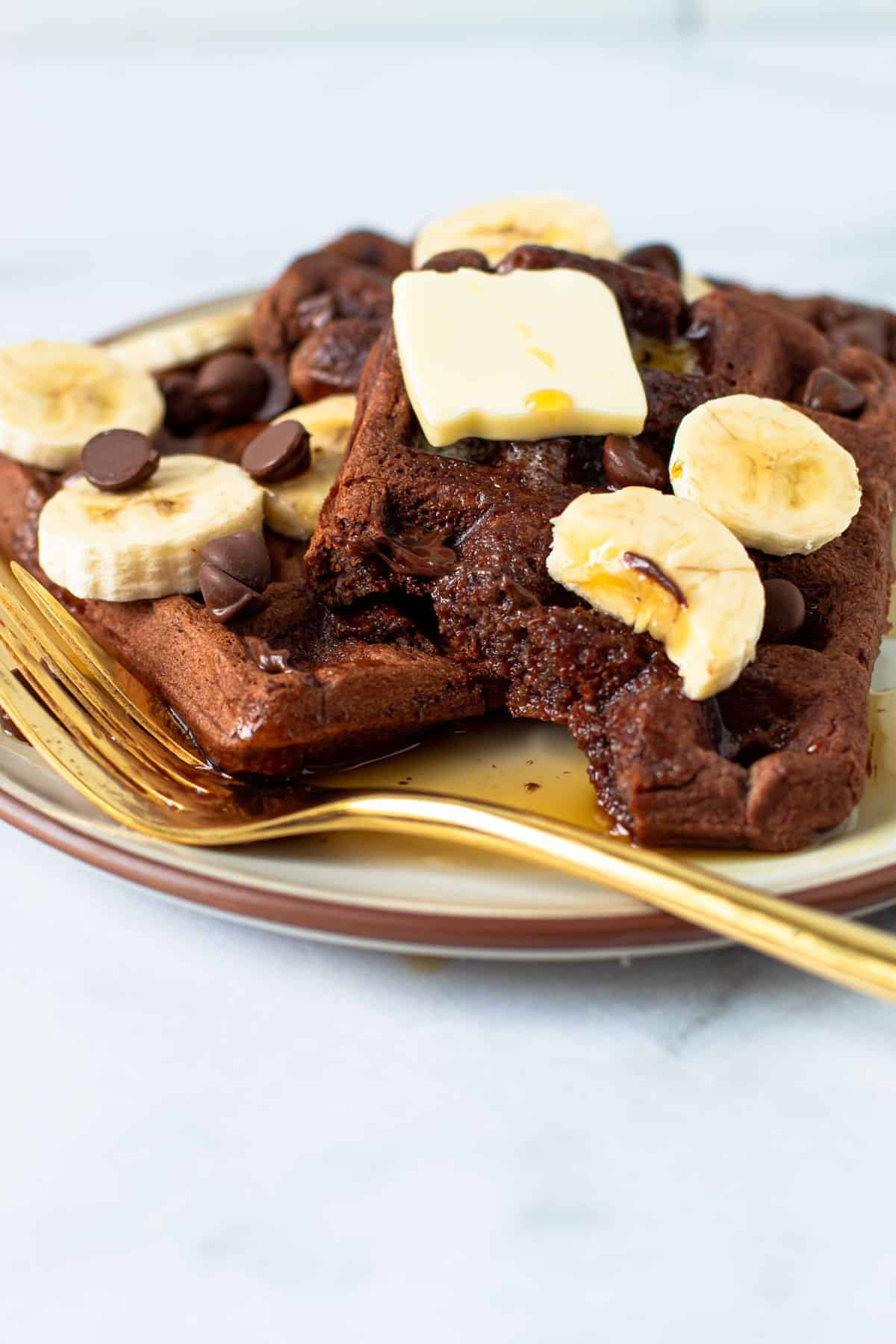 Chocolate waffles on a plate with butter and bananas.