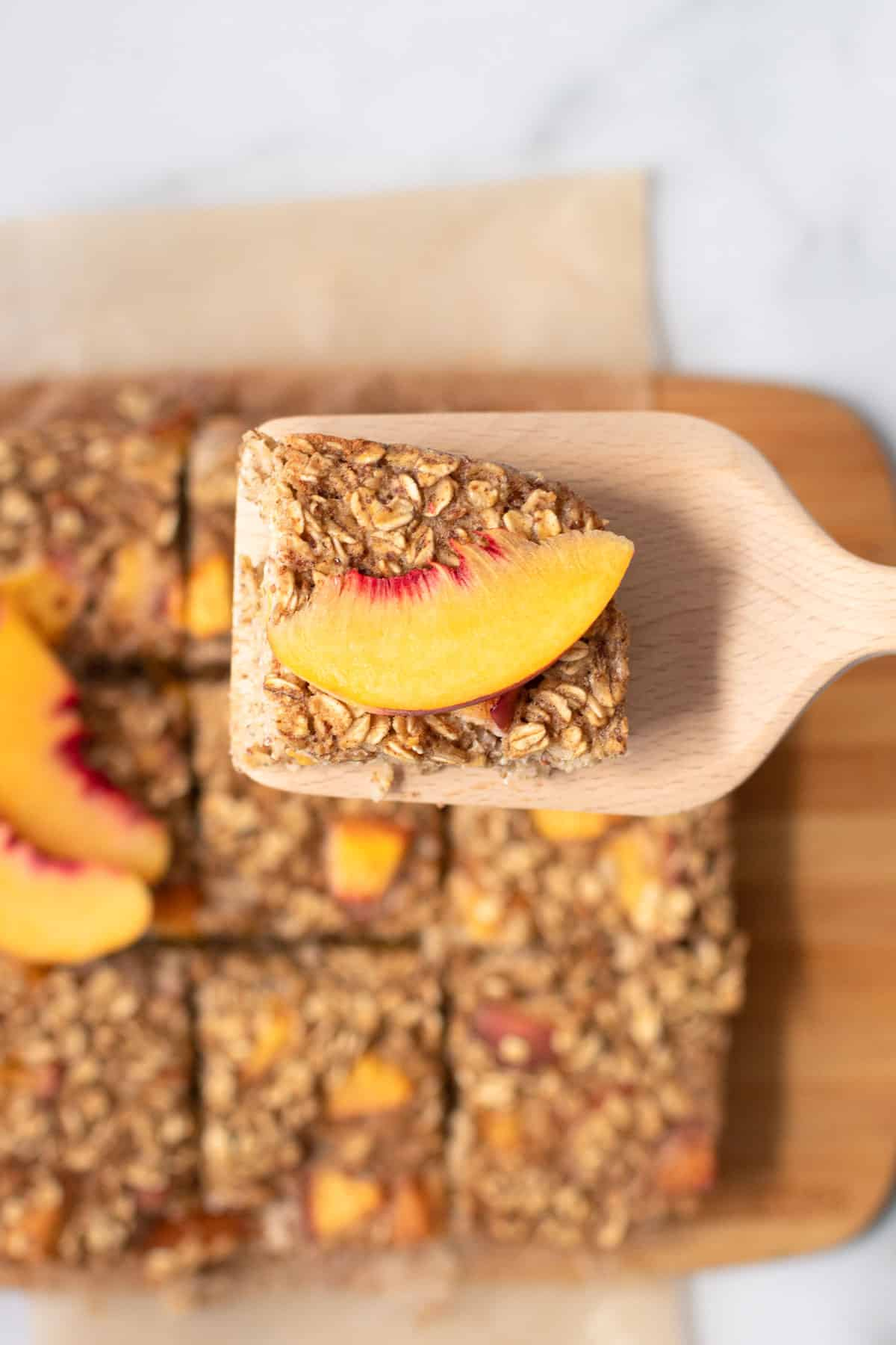 A slice of peaches and cream oatmeal on a wooden spatula with a fresh peach on it.