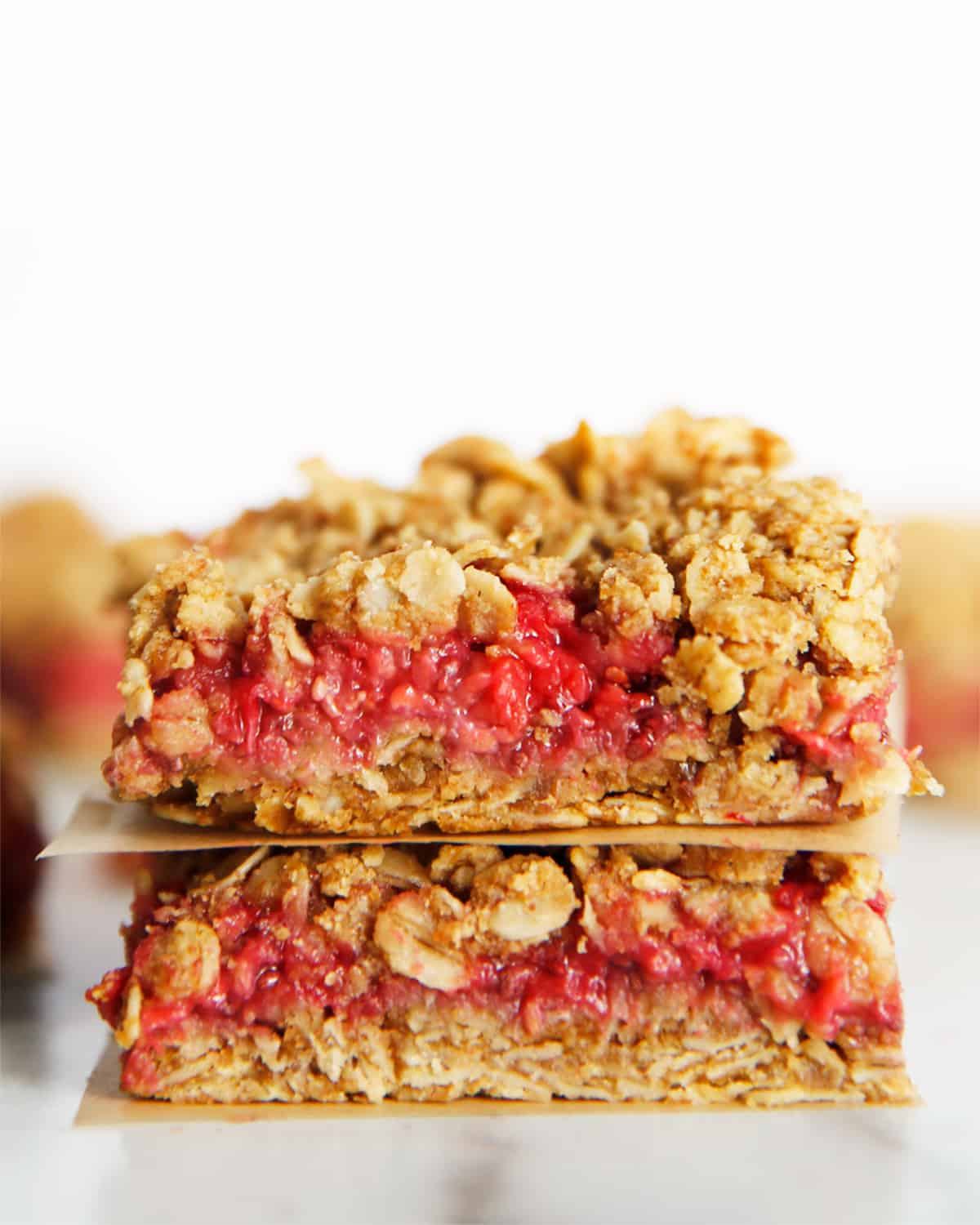 Raspberry breakfast bars stacked on top of one another.