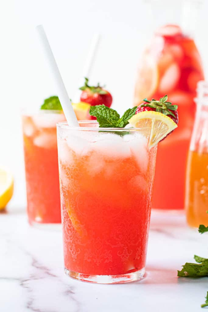 Strawberry lemonade in a glass with ice and a straw.