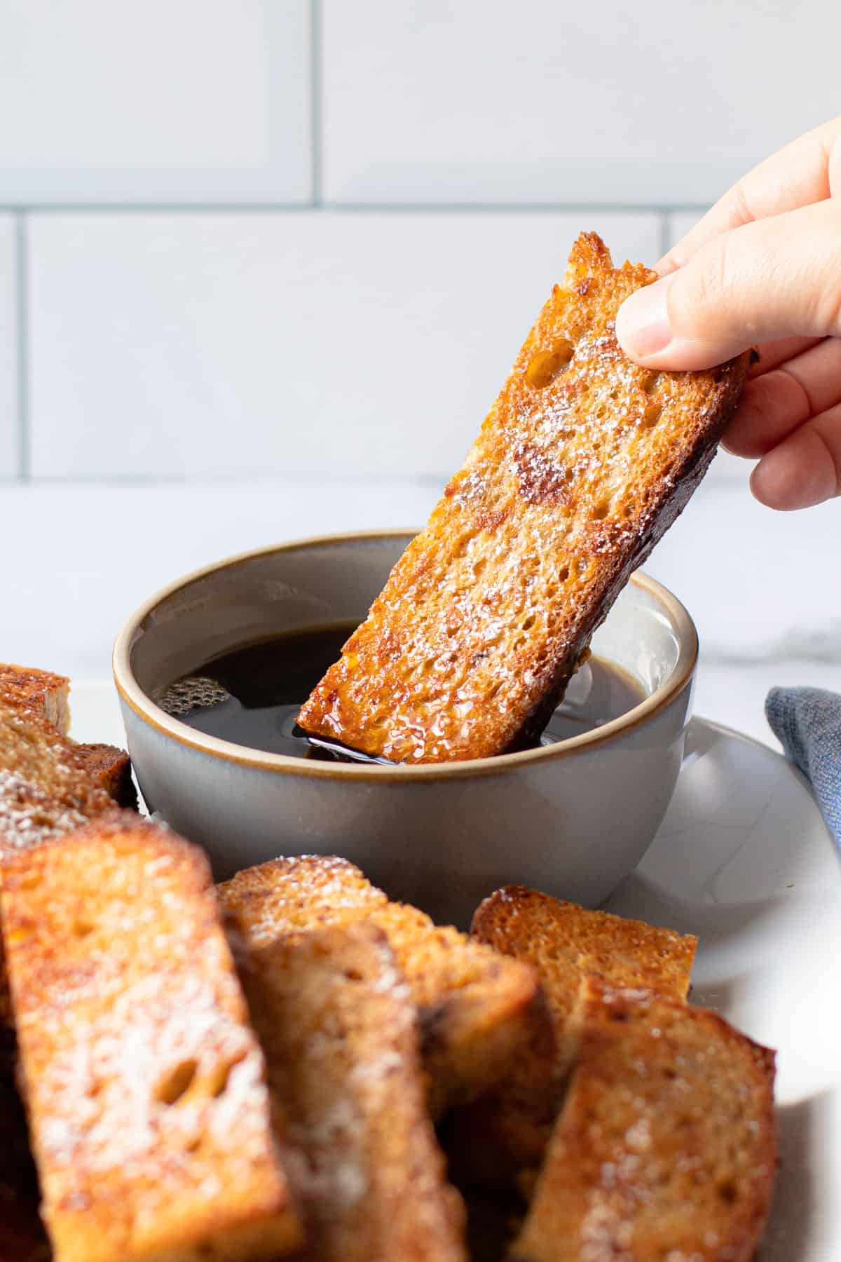 French toast sticks being dipped in maple syrup.