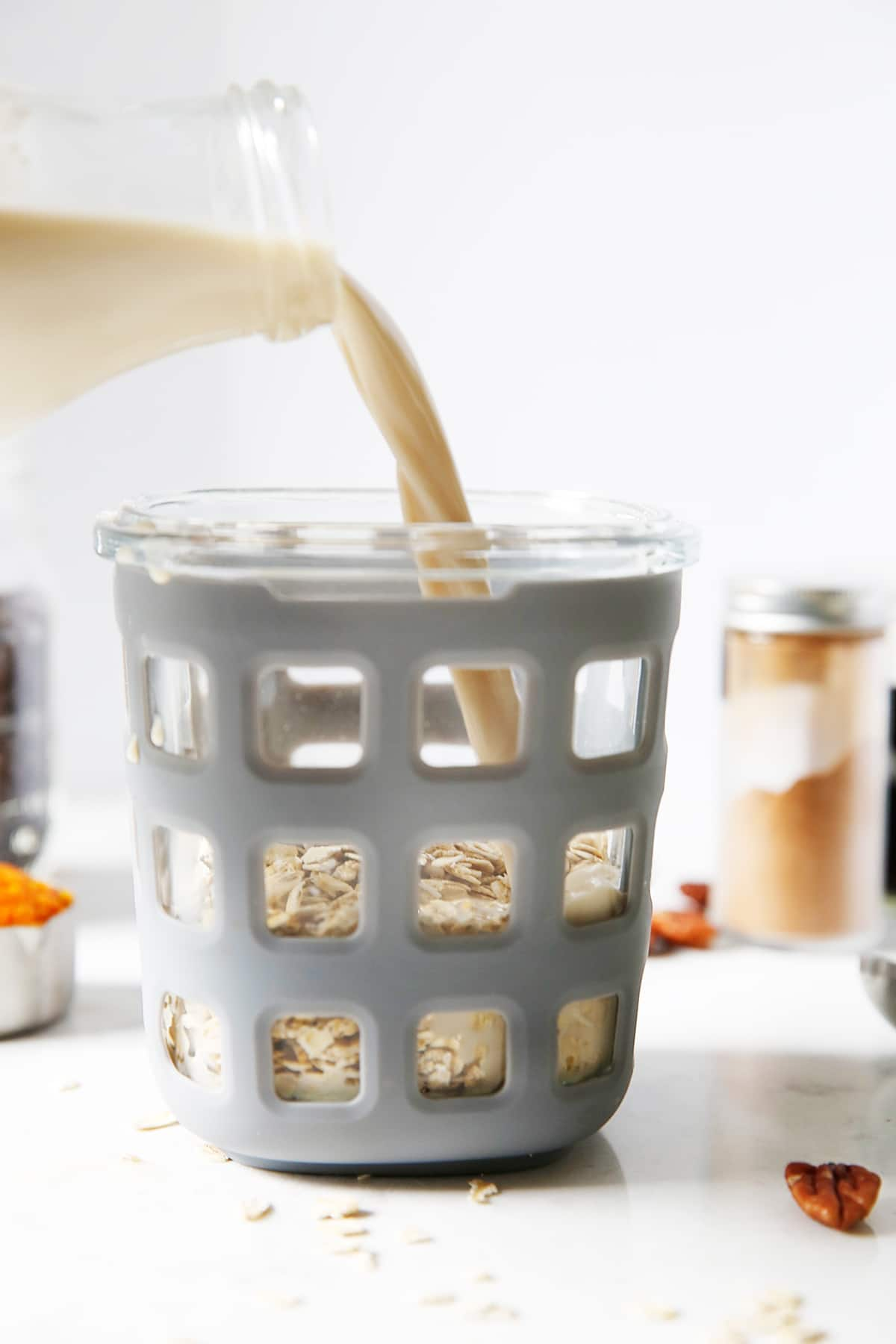 Pouring milk into overnight oats.