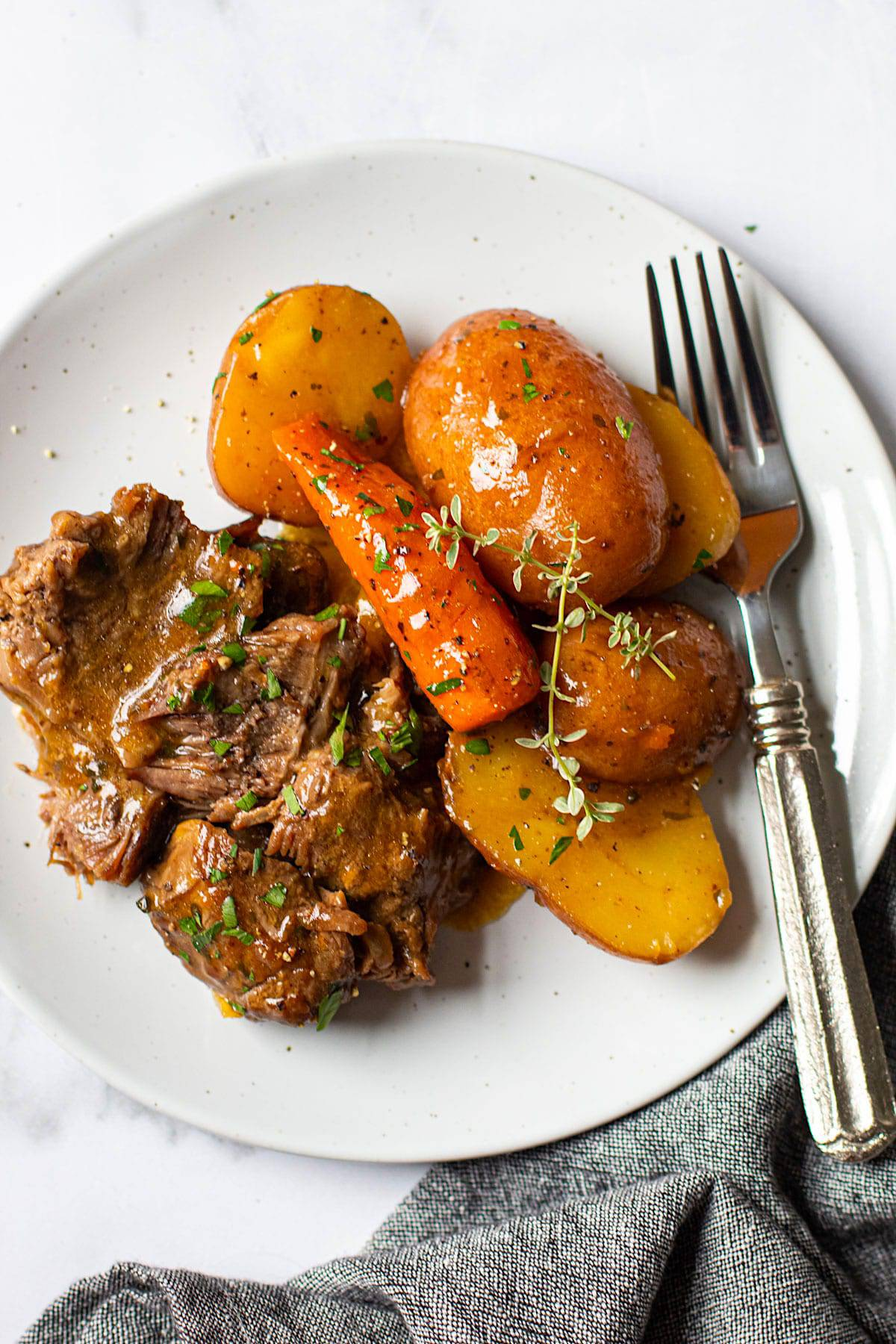 A plate of tender instant pot pot roast with carrots and potatoes.