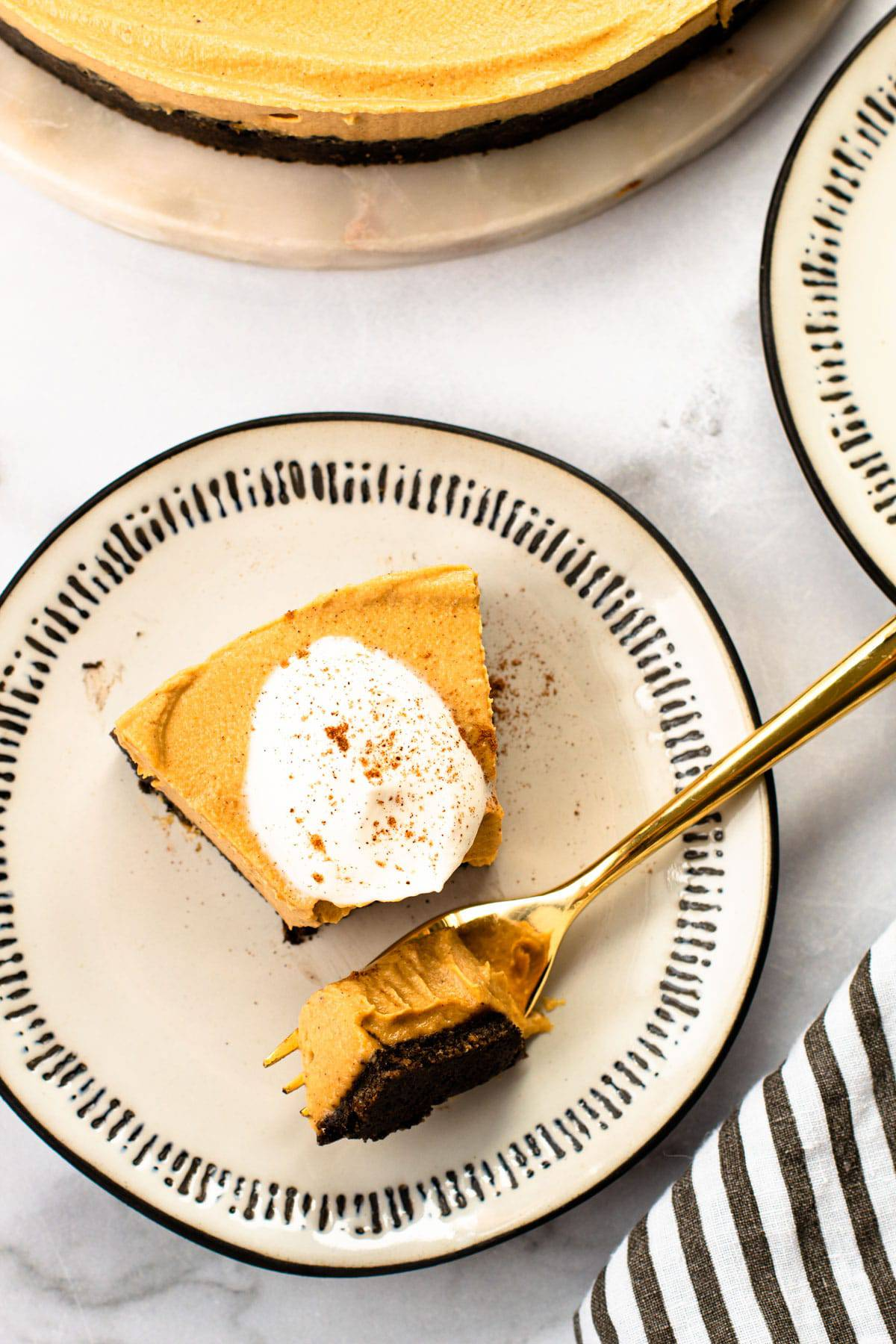 A slice of creamy vegan pumpkin cheesecake with a bite on a fork.