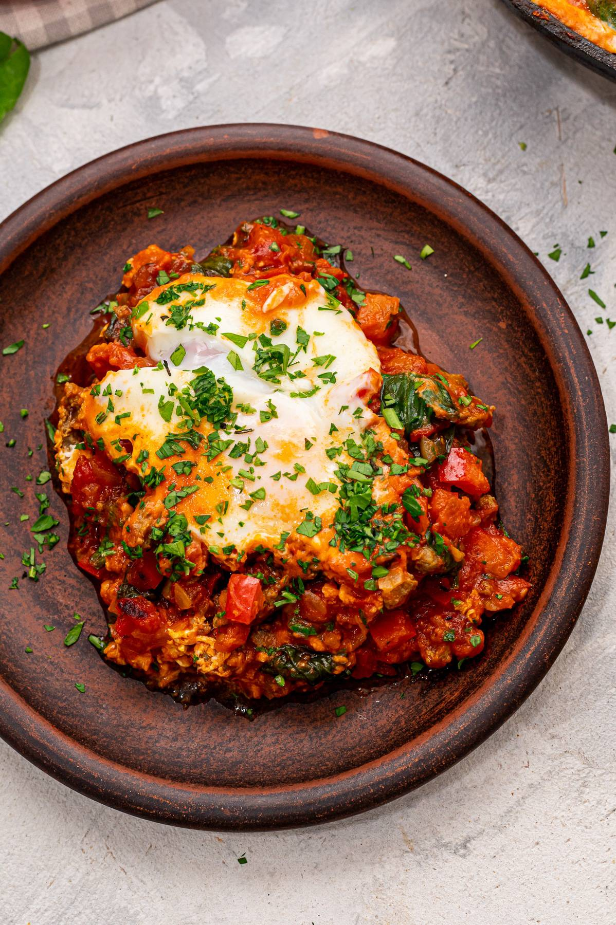 Shakshuka with parsley on top on a plate.