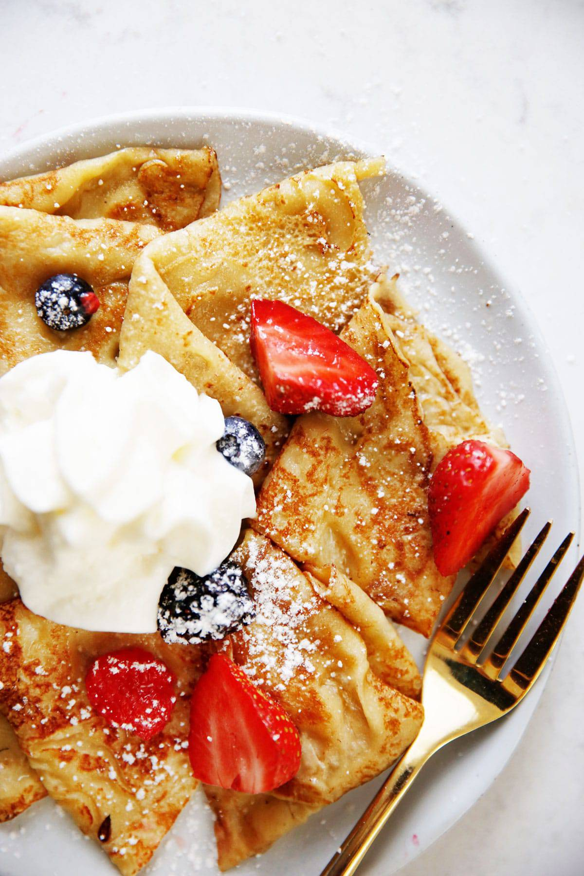 Gluten-free crepes with powdered sugar, fruit and whipped cream on a plate.