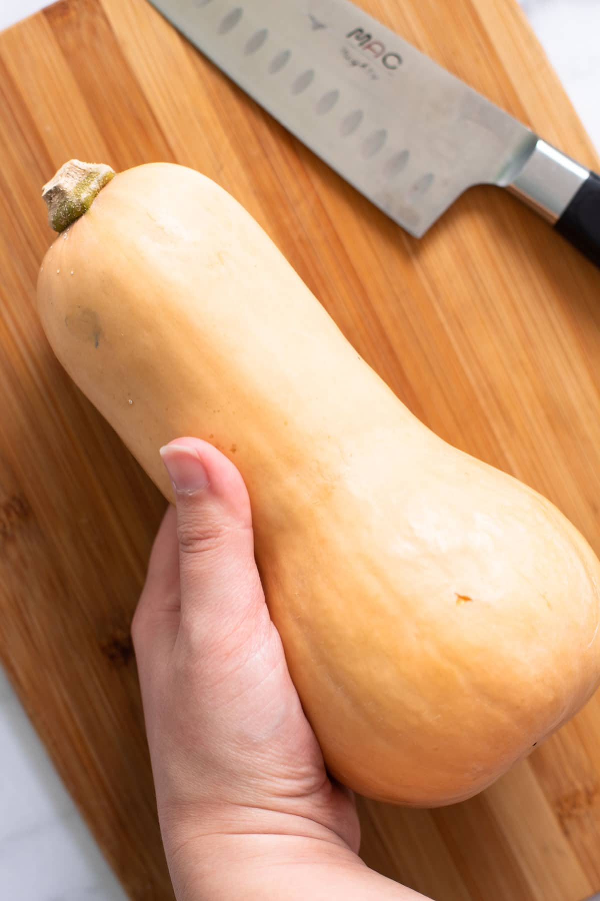 A whole butternut squash waiting to be cut up.
