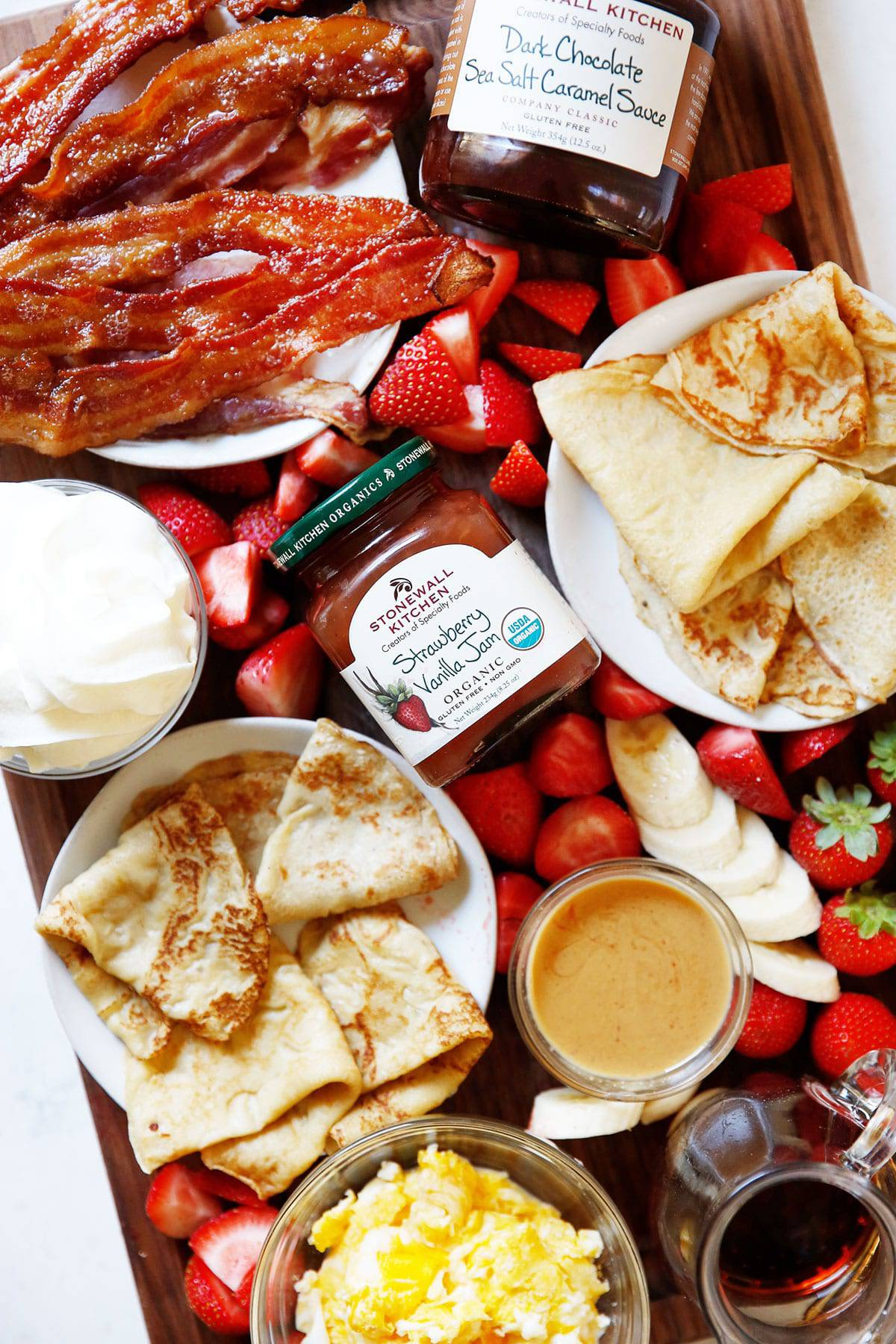 A diy crepe bar on a board with fruit, jams, eggs and bacon.