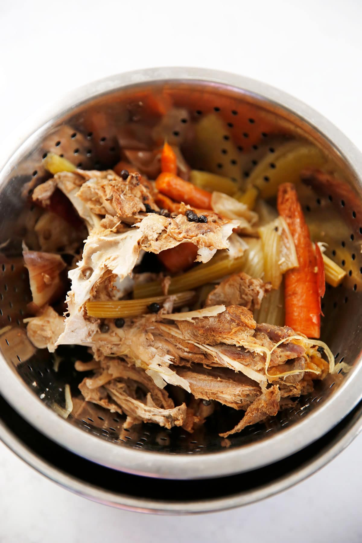 Turkey carcass and veggies being strained after cooking