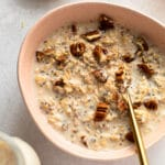 Eggnog overnight oats in a bowl with pecans on top.