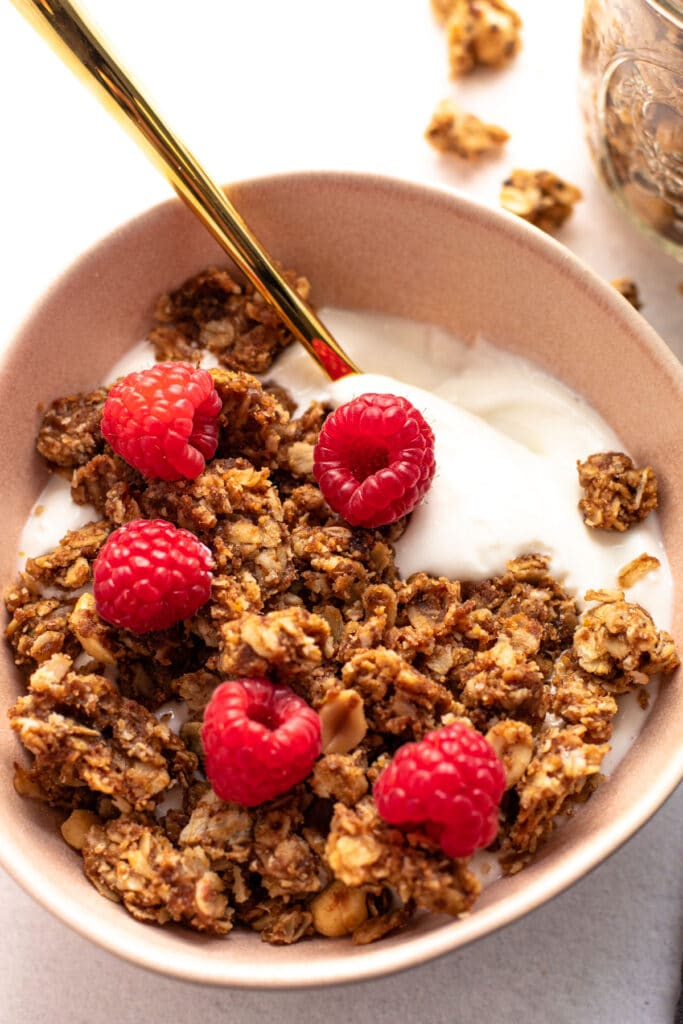 A bowl of peanut butter and jelly granola with fresh raspberries.
