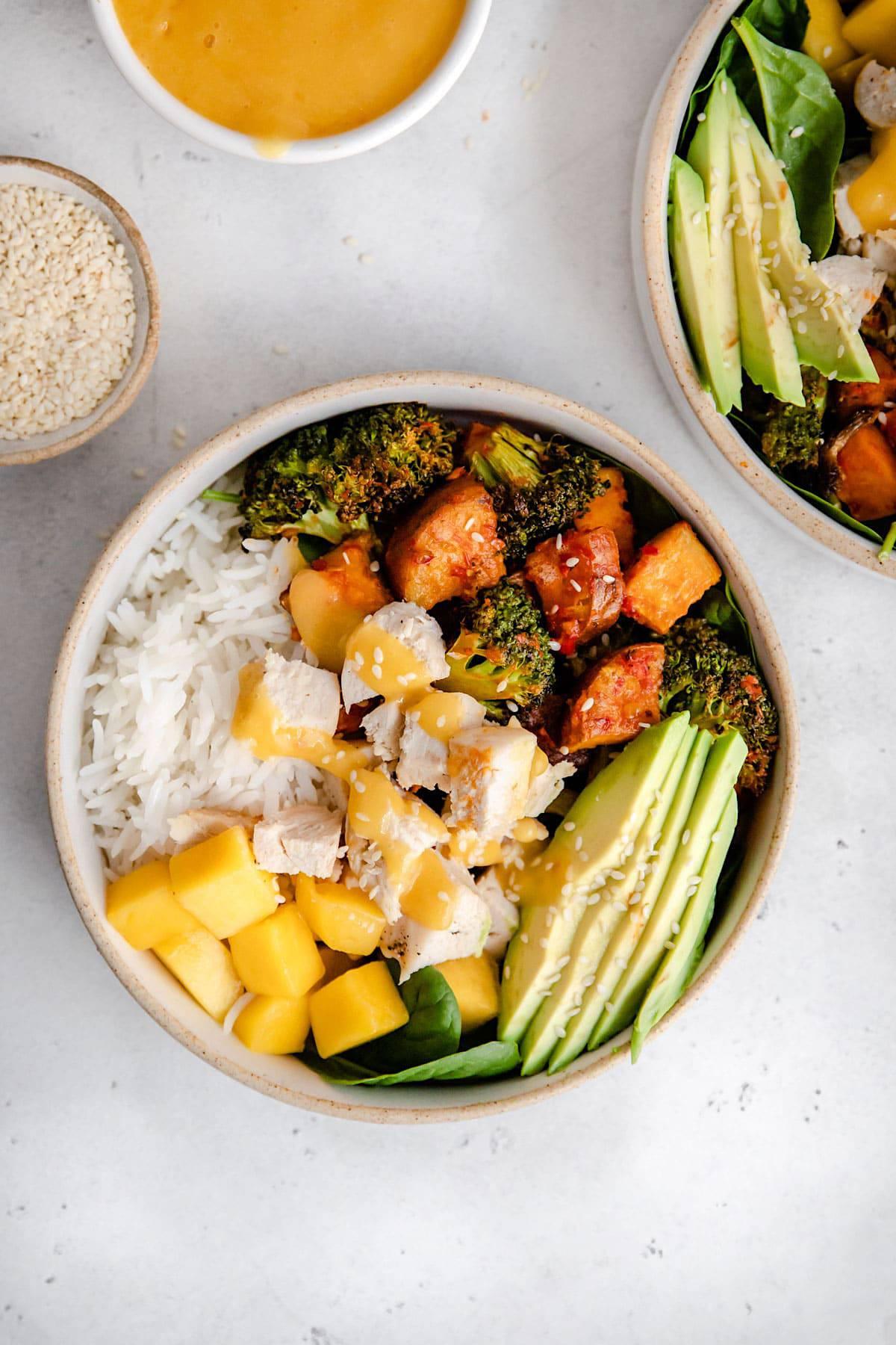 A buddha bowl with chicken, avocado, mango and sweet potato.