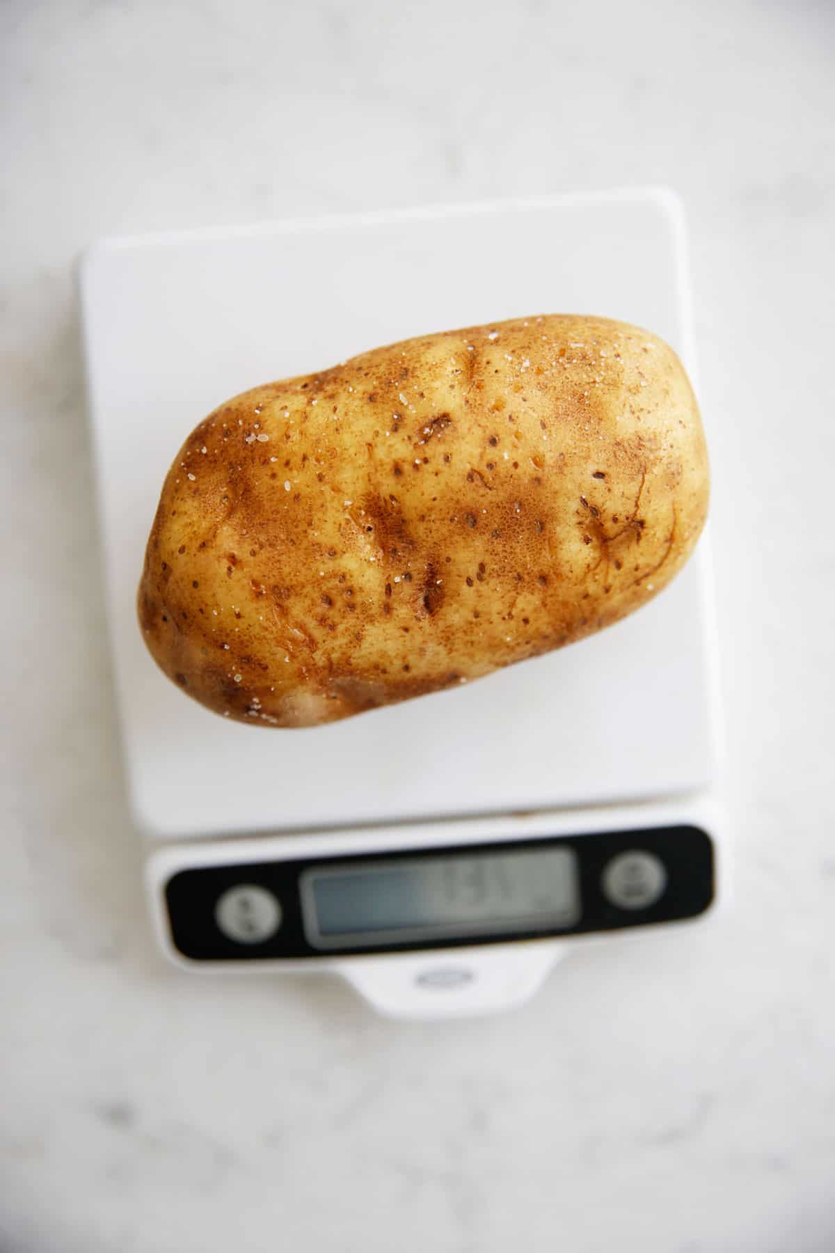 A potato on a scale to measure the size.
