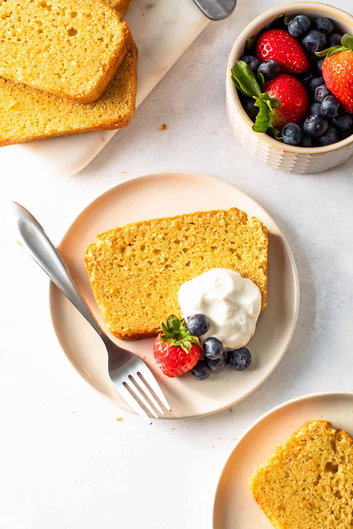 Gluten-free pound cake on a plate with whipped cream and berries.