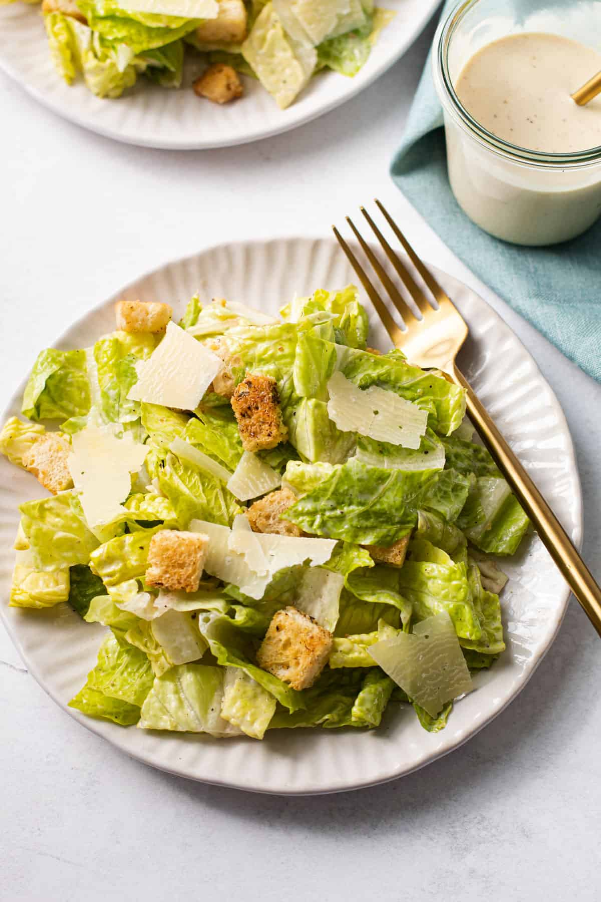 A classic Caesar salad on a plate with a fork.