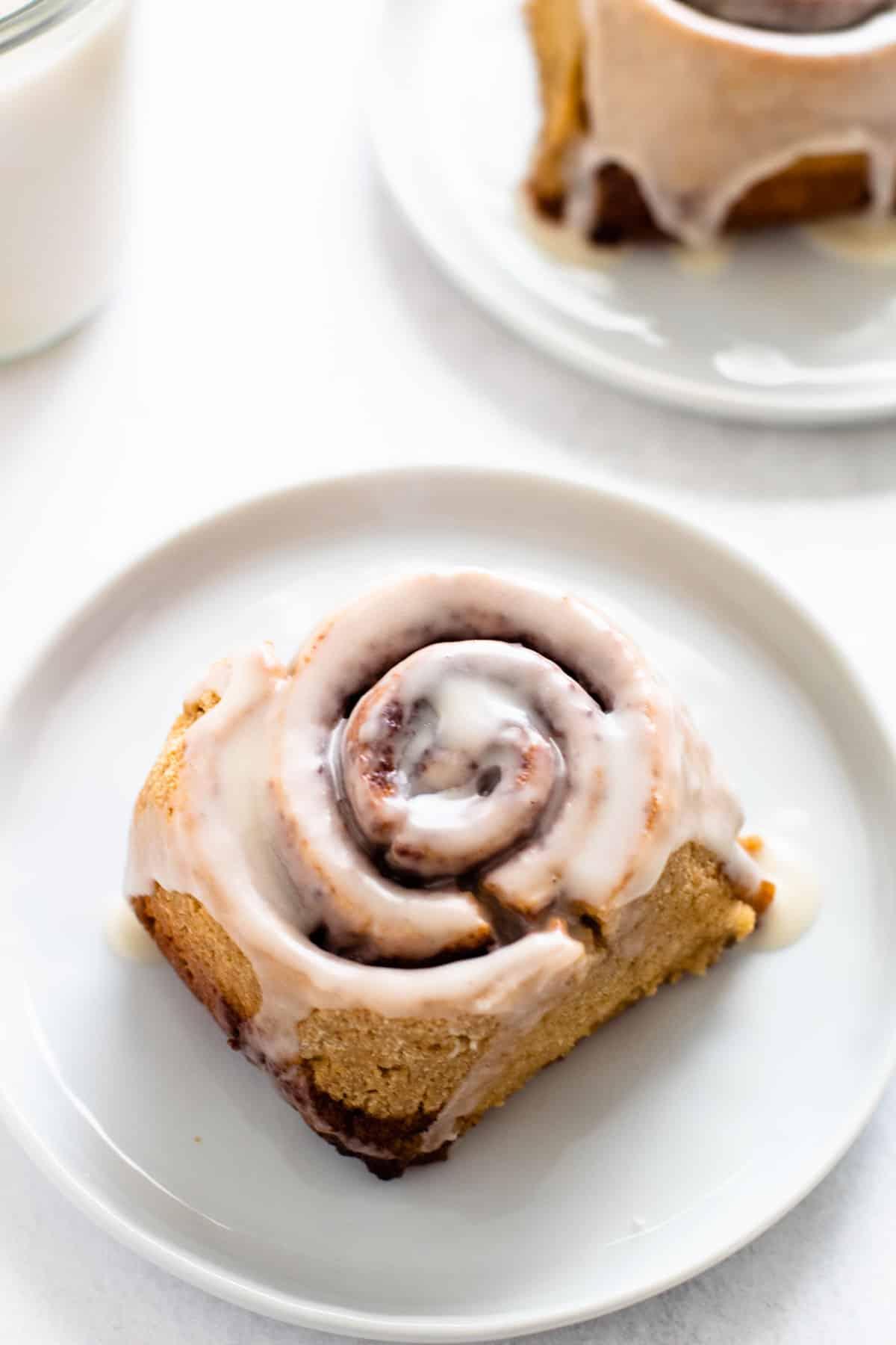 A gluten-free cinnamon roll on a plate.